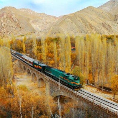 Eisenbahn auf einer Brücke zwischen Bergen und Wald